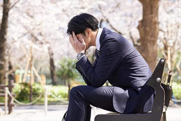 桜さくベンチで頭を抱えるサラリーマン