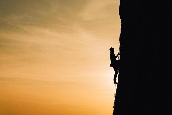 垂直な岩壁を登る男性