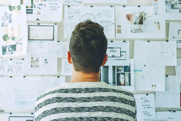 多くの選択肢をメモ書きして壁に張り検討する男性